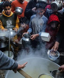 غزة..الحطاب يطهو الجريشة والعدس ويوزعها على الفقراء والمحتاجين